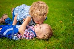 Dos hermanos que juegan en el césped en el parque Foto de archivo libre de regalías