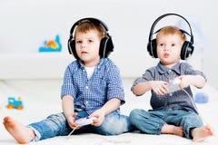 Dos hermanos que juegan en una consola de los juegos Fotos de archivo libres de regalías