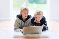 Dos hermanos que mienten en el piso con el ordenador portátil Fotos de archivo