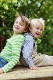Dos hermanos que se sientan de nuevo a la risa trasera Imágenes de archivo libres de regalías