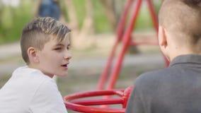 Dos hermanos que se sientan en el parque y la charla Muchachos de balanceo de la mujer en el fondo metrajes