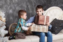 Dos hermanos que se sientan en la cama que abre los regalos del Año Nuevo en cajas Navidad imagen de archivo