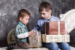Dos hermanos que se sientan en la cama que abre los regalos del Año Nuevo en cajas Navidad imágenes de archivo libres de regalías