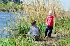 Dos hermanos que sostienen las cañas de pescar en la orilla Fotografía de archivo