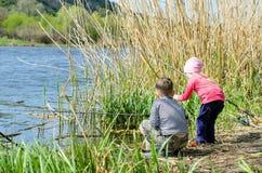Dos hermanos que sostienen las cañas de pescar en la orilla Imagenes de archivo