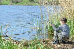 Dos hermanos que sostienen las cañas de pescar en la orilla Fotos de archivo