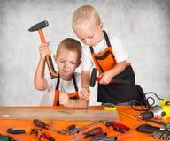 Dos hermanos que trabajan en el taller de la carpintería Martille los clavos en un tablón de madera fotos de archivo