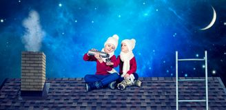 Dos hermanos se sientan el noche de la Navidad en el tejado y beben té caliente de una botella de termo ¡Feliz Navidad y buenas f foto de archivo libre de regalías