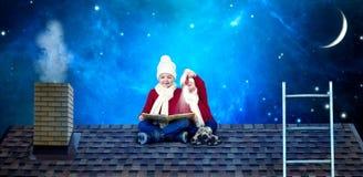 Dos hermanos se sientan el noche de la Navidad en el tejado y leen un libro con cuentos de hadas Antes de milagros de la Navidad imágenes de archivo libres de regalías