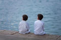 Dos hermanos se sientan en la playa y miran el mar Fotos de archivo