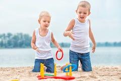 Dos hermanos son que caminan y que juegan en la playa El juego es un lanzamiento del anillo fotos de archivo libres de regalías