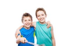 Dos hermanos sonrientes del muchacho del niño que sostienen el teléfono móvil o el palillo del selfie del smartphone que toma la  Fotografía de archivo libre de regalías