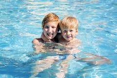 Dos hermanos sonrientes en la piscina Fotos de archivo