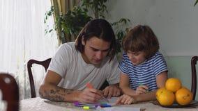 Dos hermanos un adulto y un pequeño muchacho que se sientan en la tabla y la imagen hermosa del drenaje del hombre en el papel co almacen de metraje de vídeo
