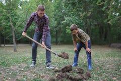 Dos hermanos una tierra del empuje en un parque para plantar el árbol joven Trabajo de la familia, día del otoño imagen de archivo libre de regalías