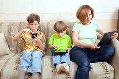 Dos hermanos y la madre se sientan en el diván imágenes de archivo libres de regalías