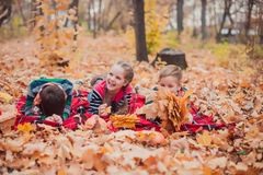 Dos hermanos y una hermana, poniendo en las hojas de otoño foto de archivo