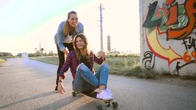 Dos hermosos y mujeres jovenes que se divierten con el monopatín