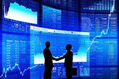 Dos hombre de negocios Handshaking con la pantalla azul de los datos foto de archivo libre de regalías