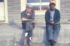 Dos hombres abajo en su suerte que se sienta en un banco Imágenes de archivo libres de regalías