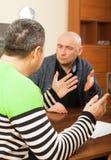 Dos hombres adultos que discuten algo en la tabla Foto de archivo libre de regalías
