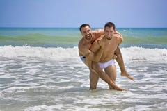 Dos hombres alegres el vacaciones de la playa Foto de archivo libre de regalías