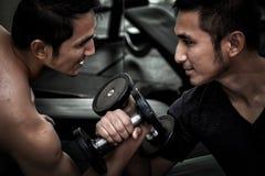 Dos hombres asiáticos utilizan la brazo-lucha c del levantamiento de pesas del ejercicio de la pesa de gimnasia foto de archivo
