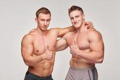 Dos hombres atléticos que gesticulan los pulgares para arriba Fotografía de archivo
