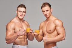 Dos hombres atléticos con los vidrios de zumo de naranja Imagen de archivo libre de regalías