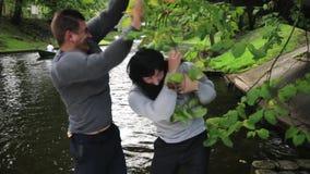 Dos hombres atractivos en trajes falsos del músculo en ramas de árbol flotantes del golpe del barco almacen de video