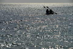 Dos hombres baten un kajak en el mar fotos de archivo