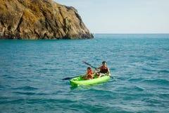 Dos hombres baten un kajak en el mar El Kayaking en la isla Foto de archivo libre de regalías