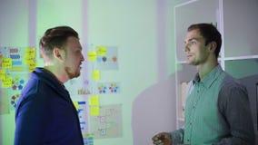 Dos hombres comunican la situación en la oficina almacen de metraje de vídeo