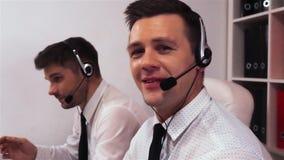 Dos hombres con las auriculares que hablan en centro de llamada de voz almacen de metraje de vídeo