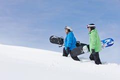 Dos hombres con las snowboard en Ski Holiday In Mountains Foto de archivo libre de regalías