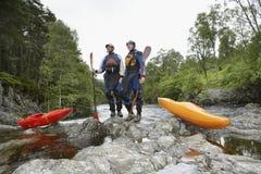 Dos hombres con los kajaks por el río Foto de archivo libre de regalías