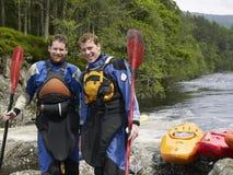 Dos hombres con los kajaks por el río Fotos de archivo libres de regalías