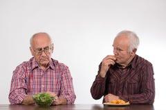 Dos hombres con sano y la comida basura foto de archivo