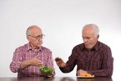 Dos hombres con sano y la comida basura imagen de archivo