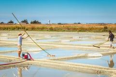 Dos hombres cosechan la sal de la manera tradicional en los saladares Imagenes de archivo