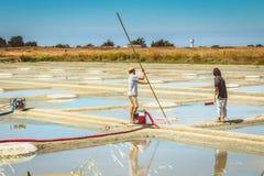 Dos hombres cosechan la sal de la manera tradicional en los saladares Foto de archivo