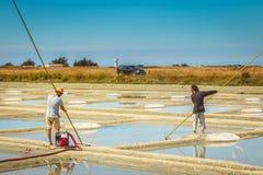 Dos hombres cosechan la sal de la manera tradicional en los saladares Fotos de archivo libres de regalías