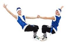 Dos hombres de la Navidad en santa azul visten el baile contra blanco aislado en integral fotografía de archivo