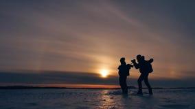 Dos hombres de la silueta de los turistas van a los viajeros de la puesta del sol fotógrafos de las personas del concepto dos del almacen de metraje de vídeo
