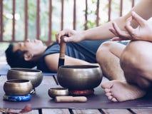 Dos hombres de la yoga hacen la yoga al aire libre con los cuencos del canto fotos de archivo