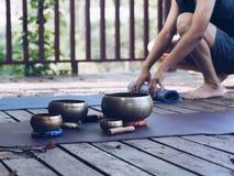 Dos hombres de la yoga hacen la yoga al aire libre con los cuencos del canto foto de archivo libre de regalías