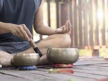 Dos hombres de la yoga hacen la yoga al aire libre con los cuencos del canto imagen de archivo libre de regalías
