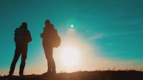 dos hombres de los caminantes de los turistas con las mochilas en la puesta del sol van a caminar viaje hikers almacen de metraje de vídeo
