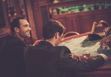 Dos hombres de moda detrás de la tabla en un casino imagen de archivo