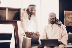 Dos hombres de negocios árabes que miran en el ordenador portátil junto imagenes de archivo